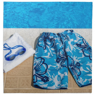 Swimming trunks goggles and towel at pool napkin