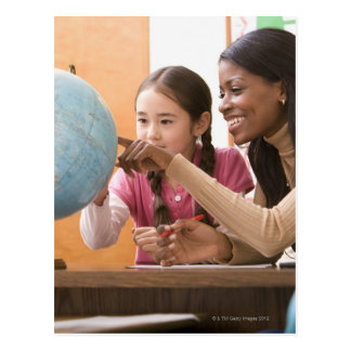 Teacher and student looking at globe postcard