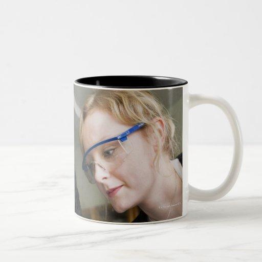 Teacher assisting student in laboratory coffee mugs