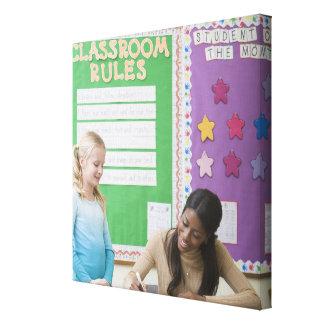 Teacher grading girls paper in classroom canvas print