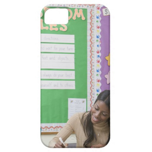 Teacher grading girls paper in classroom iPhone 5 covers