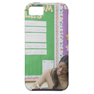 Teacher grading girls paper in classroom iPhone 5 cover