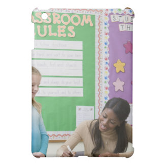 Teacher grading girls paper in classroom iPad mini cover