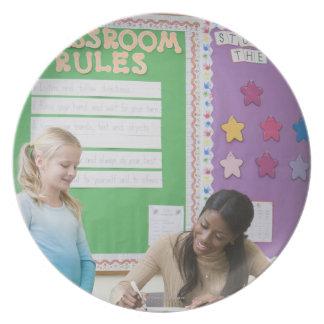 Teacher grading girls paper in classroom dinner plates