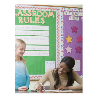 Teacher grading girls paper in classroom postcard