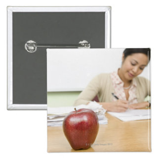 Teacher grading papers with apple in foreground 15 cm square badge