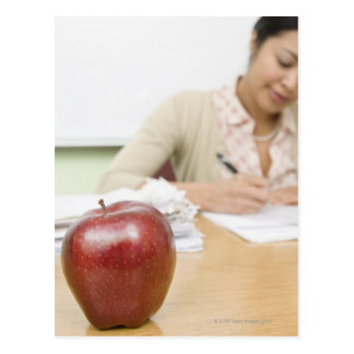 Teacher grading papers with apple in foreground postcards