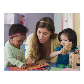 Teacher helping toddlers color at daycare postcard