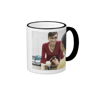 Teacher talking to student in laboratory mugs