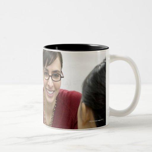 Teacher talking to student in laboratory mugs