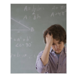 Teenaged boy in front of blackboard with math poster