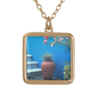 TERRA COTTA VASE; BLUE WALL; WHITE STAIRCASE; PINK GOLD PLATED NECKLACE