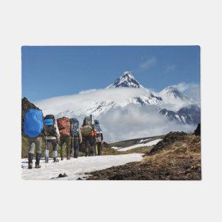 Travelers climb on mount on background volcanoes doormat
