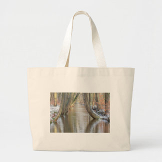 Tree trunks and forest stream  with snow in winter large tote bag