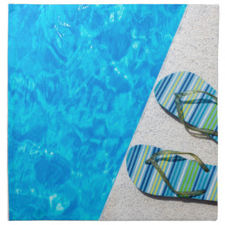 Two bathing slippers on edge of swimming pool napkin