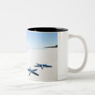 Two blue starfish at water's edge on tropical 2 Two-Tone coffee mug