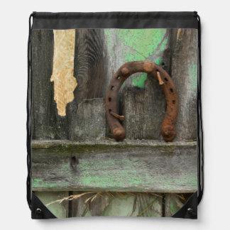 USA, Montana. Rusty horseshoe on old fence Drawstring Bag