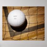 Volleyball and net on hardwood floor