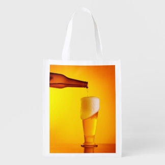 Waiter pouring beer, glass of a cold drink reusable grocery bag