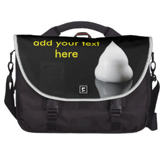 white blob of cream is reflected in black backgrou laptop computer bag