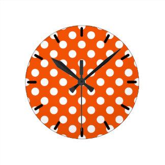 White polka dots on orange round clock