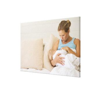 Woman breastfeeding baby canvas prints