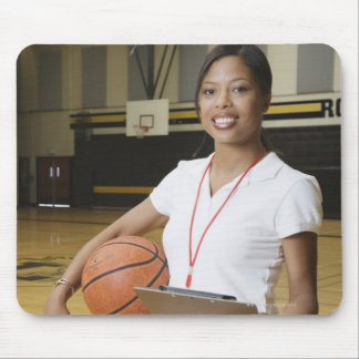 Woman holding basketball and clipbpard, smiling, mouse pad