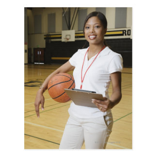 Woman holding basketball and clipbpard, smiling, postcard