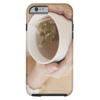 Woman holding cup with chamomile tea tough iPhone 6 case