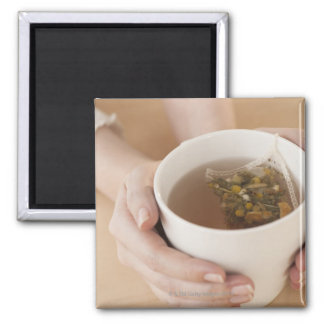 Woman holding cup with chamomile tea magnet