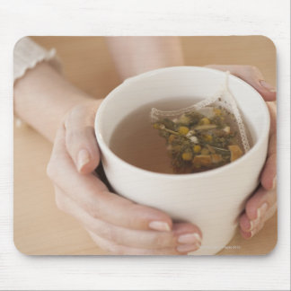 Woman holding cup with chamomile tea mouse pad