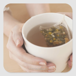 Woman holding cup with chamomile tea square sticker