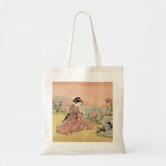 Woman picking chrysanthemums tote bag