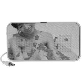 Woman relaxing in hot tub with flower petals, iPod speaker