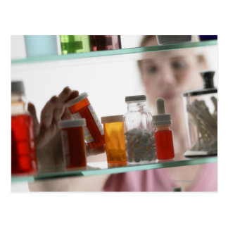 Woman taking pills from medicine cabinet postcard