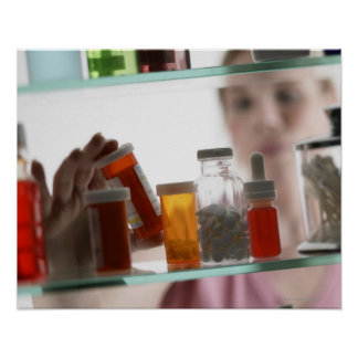 Woman taking pills from medicine cabinet print