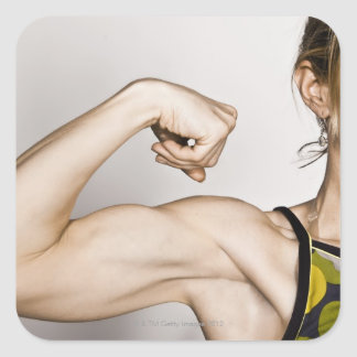 Young blond female flexes bicep muscle while square sticker