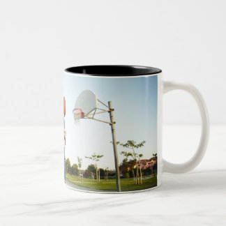 Young man and senior man on outdoor basketball Two-Tone coffee mug