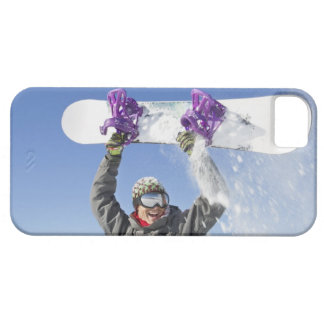 Young man holding his snowboard above his head iPhone 5 covers