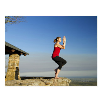 young woman practices yoga on a bluff in the postcard